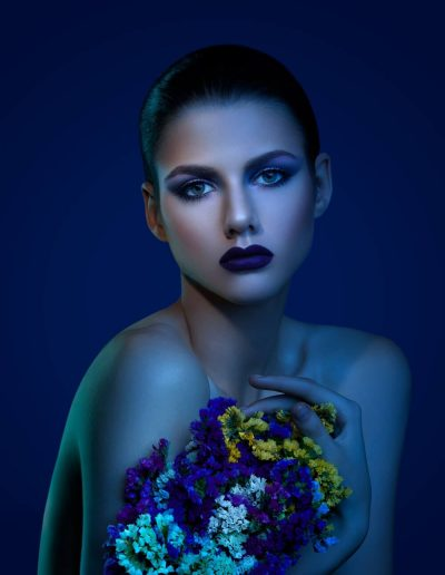 A colorful portrait of a young girl with makeup taken on a blue background holding a colorful bouquet of flowers and watching into photographer's Canon camera