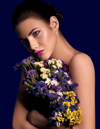 Portrait of a young girl holding a bouquet of colorful spring flowers