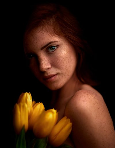 A portrait image taken by Samuel Zlatarev of a young girl with freckles holding yellow tulips in her hands and watching in the camera