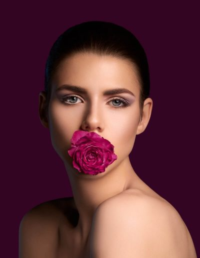 A beautiful portrait of a naked young girl holding red peony rose in her mouth