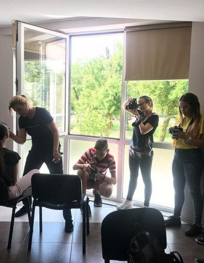 A group of people take pictures of a professional model on Samuel Zlatarev's photography workshop in Plovdiv