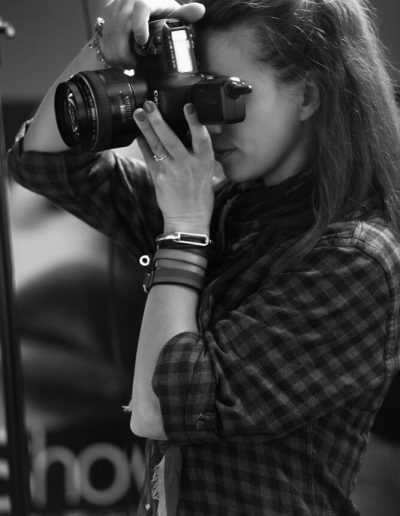 A young woman taking pictures in a photography studio with Canon camera
