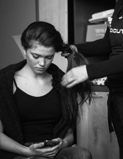 A young freckles model chatting on her phone while her hair is getting ready