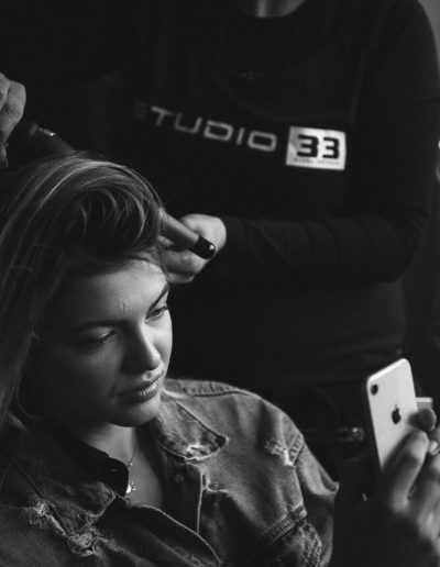 Black and white image of a model taking selfie while her hair is getting ready for photoshoot